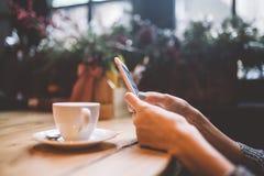 Remet le plan rapproché de beaux d'une jeune utilisations fille, types texte à un téléphone portable à une table en bois près d'u photographie stock libre de droits