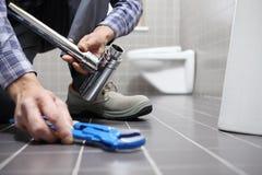 Remet le plombier au travail dans une salle de bains, mettant d'aplomb le service des réparations, As photographie stock libre de droits
