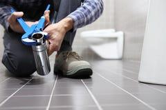 Remet le plombier au travail dans une salle de bains, mettant d'aplomb le service des réparations, As photographie stock
