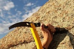 Remet le roche-grimpeur martelant dans le crochet dans la roche photographie stock libre de droits