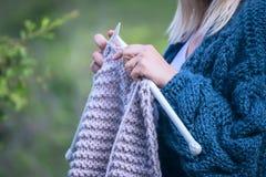Remet le tricotage en gros plan sur des aiguilles de tricotage, knit gris de laine contre le contexte d'un jardin naturel Photos libres de droits
