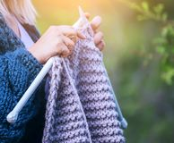 Remet le tricotage en gros plan sur des aiguilles de tricotage, knit gris de laine contre le contexte d'un jardin naturel Photo stock