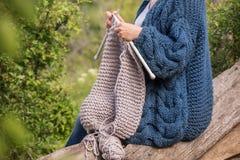 Remet le tricotage en gros plan sur des aiguilles de tricotage, knit gris de laine contre le contexte d'un jardin naturel Photographie stock