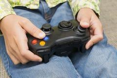 Remet tenir un contrôleur de manette tout en jouant des jeux vidéo Image stock