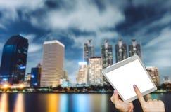 Remettez à comprimé de prise l'écran vide sur la table avec le paysage urbain de Bangkok Thaïlande photographie stock