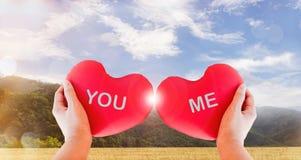 Remettez à des couples de prise le coeur rouge avec le texte vous et moi sur le backgr de nature Photo stock
