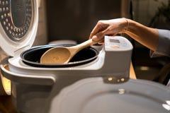 Remettez à prise la poche en bois dans le cuiseur de riz électrique Photos stock