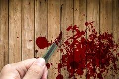 Remettez à prise le coupeur rouillé de couteau avec le grunge du sang sur le bois photographie stock