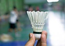 remettez à prise le shuttercock blanc plus de brouillé de la cour de badminton avec Photo stock