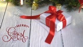 Remettez écrire le texte blanc de lettrage de calligraphie d'animation de Joyeux Noël sur le fond en bois blanc avec des cadeaux  banque de vidéos