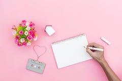 Remettez écrit sur la vue supérieure de carnet de grille avec le backgroun rose doux Image stock