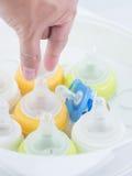 Remettez atteignent pour sélectionner le mamelon dans le stérilisateur de vapeur de mamelon Photographie stock libre de droits