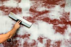 Remettez avec attacher du ruban adhésif au couteau plâtrant le mur photo libre de droits