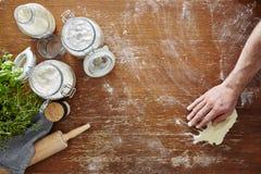 Remettez essuyer la farine sur la scène atmosphérique de cuisine d'espace de travail en bois Photos stock