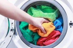 Remettez et mettez la blanchisserie dans la machine à laver image stock