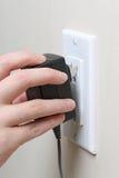 Remettez insérer une prise électrique dans une prise murale Photo stock