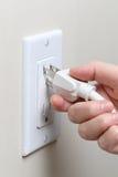 Remettez insérer une prise électrique dans une prise murale Image stock