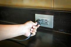Remettez insérer une prise électrique dans une prise murale Photos libres de droits