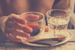Remettez juger fraîchement brassé de l'americano chaud de café noir Photographie stock libre de droits