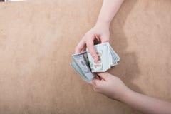 Remettez juger le dollar américain d'isolement sur le fond en bois photo stock