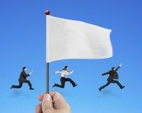 Remettez juger le drapeau avec le fonctionnement d'hommes d'affaires d'isolement sur le bleu Photo libre de droits