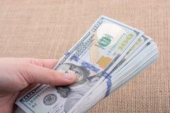 Remettez juger le paquet de billet de banque du dollar US disponible Photos libres de droits