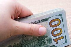 Remettez juger le paquet de billet de banque du dollar US disponible Photographie stock libre de droits