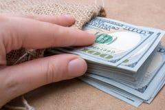 Remettez juger le paquet de billet de banque du dollar US disponible Photos stock