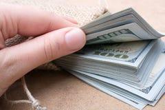 Remettez juger le paquet de billet de banque du dollar US disponible Photographie stock
