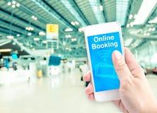 Remettez juger mobile avec la réservation en ligne avec le backgr d'aéroport de tache floue Photos libres de droits