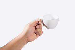 Remettez juger une tasse de café d'isolement sur le blanc Photo stock