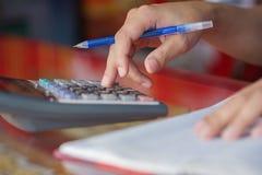 Remettez l'écriture et le compte sur la calculatrice dans le bureau images stock
