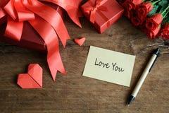 Remettez l'écriture sur le carnet avec le boîte-cadeau et la fleur rouges sur en bois Photo libre de droits