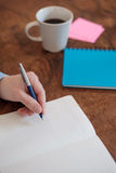 Remettez l'écriture sur un livre de copie sur la table en bois Photographie stock libre de droits