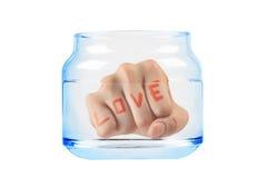 Remettez l'amour de mot dans le pot de l'eau d'isolement sur le blanc Avec le tapotement de coupure Photographie stock libre de droits