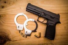Remettez l'arme à feu avec des manchettes de main sur la surface en bois photos stock