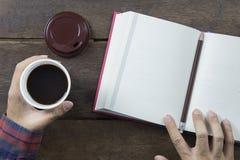 Remettez l'Asiatique d'homme tenant le café noir en la tasse en plastique blanche et le rouge Photo libre de droits