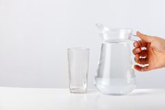 Remettez l'eau de versement de la cruche en verre au verre sur le fond blanc Image stock