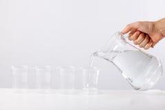 Remettez l'eau de versement de la cruche en verre au verre sur le fond blanc Photos libres de droits