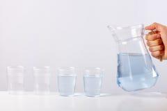 Remettez l'eau de versement de la cruche en verre au verre sur le fond blanc Images libres de droits