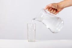 Remettez l'eau de versement de la cruche en verre au verre sur le fond blanc Photographie stock libre de droits