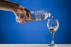 Remettez l'eau pure de versement dans un verre refoulé photographie stock