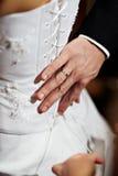 Remettez l'homme avec une boucle à une robe de la mariée Photos stock
