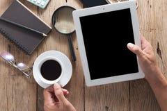 Remettez l'homme d'affaires tenant la tasse de café blanc avec le comprimé d'utilisation sur l'OE Image libre de droits