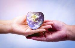 Remettez l'homme tenant la terre de coeur et écoutant le coeur Photographie stock libre de droits