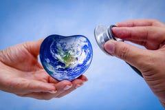 Remettez l'homme tenant la terre de coeur et écoutant le coeur Photo libre de droits