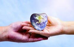 Remettez l'homme tenant la terre de coeur et écoutant le coeur Image stock