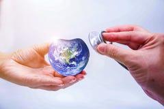 Remettez l'homme tenant la terre de coeur et écoutant le coeur Photos libres de droits