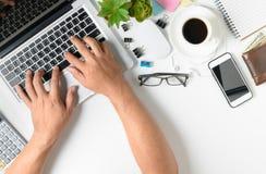 Remettez l'ordinateur portable de dactylographie d'homme sur la table blanche moderne de bureau Images stock