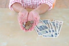 Remettez la femme avec les billets de banque et la pièce de monnaie japonais de Yens de devise Photos libres de droits